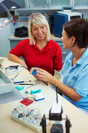 Dentist explaining a customer denture work in laboratory photo