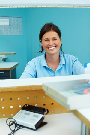 Happy dental technician working in dental laboratory photo