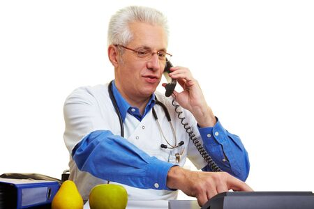 Doctor sitting at his desk and making a phone call Stock Photo - 6357971