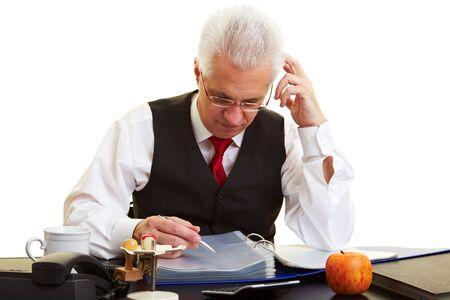 Elderly businessman reading files at his desk Stock Photo - 6357968