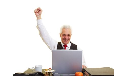 An elderly businessman with laptop clenching his fist photo