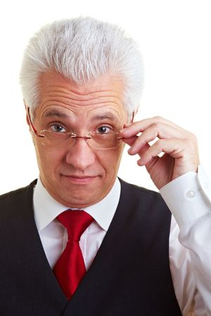 An elderly businessman looking through his glasses