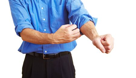 rolling up: Man rolling up his blue shirt sleeves