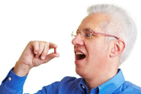 scepticism: Senior citizen taking a red pill