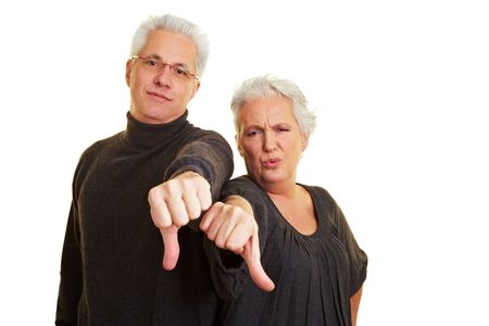 Two dissappointed senior citizens holding their thumbs down photo