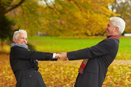 senior citizens: Happy senior couple in an autumn forest