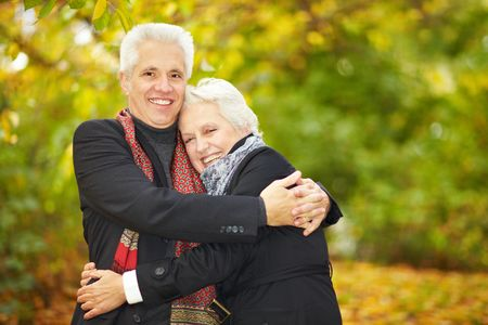 Elderly man embracing a woman in a forest photo