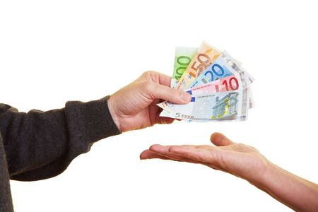 euro banknotes: Hand handing over Euro banknotes to other hand Stock Photo