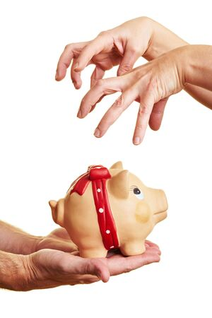 takeover: Greedy hands reaching for a piggy bank Stock Photo