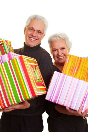 Two happy senior citizens holding colorful gifts photo