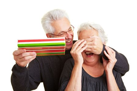 Elderly man with gift covering eyes of his wife photo