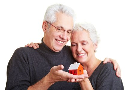 Two happy senior citizens with small red house photo