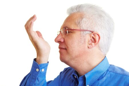 year profile: Senior citizen smelling perfume on his hand pulse