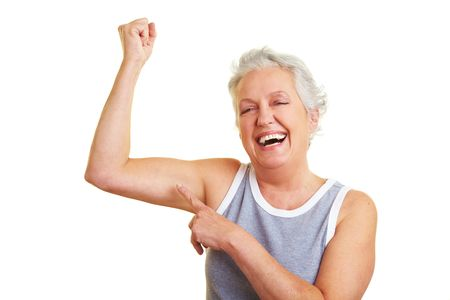 muscle woman: Happy senior woman showing her upper arm muscles