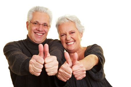year old: Two happy senior citizens holding their thumbs up Stock Photo