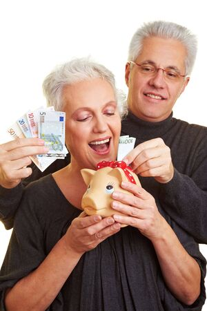 provision: Senior citizen putting banknotes in a piggy bank