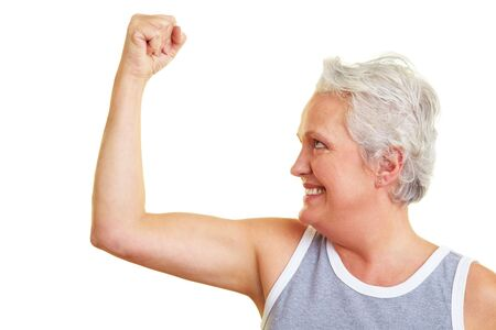 arm muscles: Happy senior woman showing her upper arm muscles