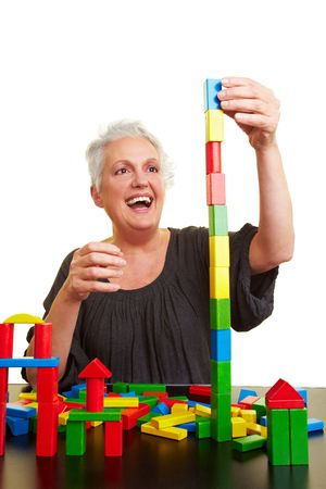 demented: Happy senior woman with many colorful building blocks