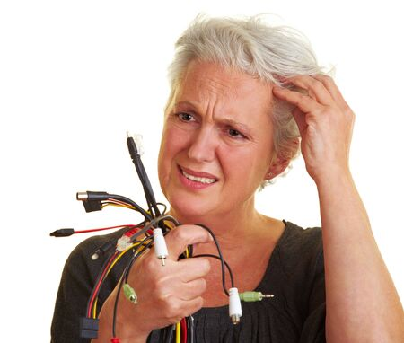 Senior woman looking at many different cables photo