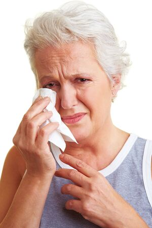 saddened: Crying senior woman drying her tears with handkerchief