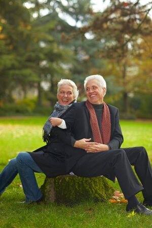 50 years old man: Happy senior couple sitting on a tree trunk