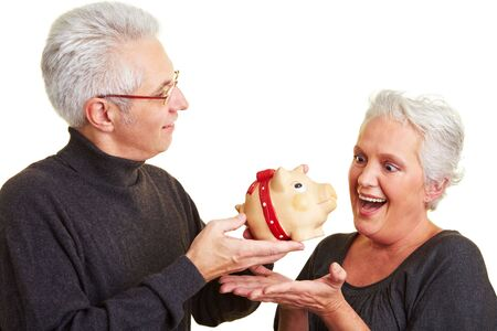 Elderly man giving a piggy bank to his woman photo