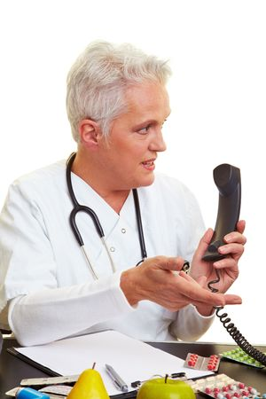 Doctor sitting at his desk and making a phone call Stock Photo - 6398174