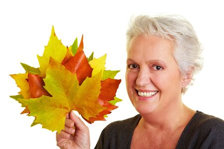 Happy senior woman with many colorful maple leaves photo