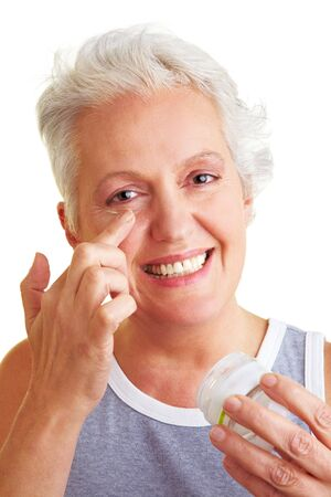 mensch: Happy senior woman applying lotion to her face