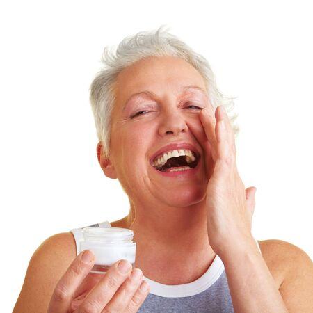 Happy femme senior application lotion pour le visage