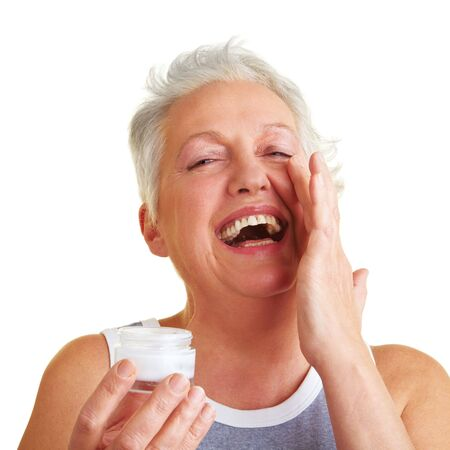 aging skin: Happy senior woman applying lotion to her face