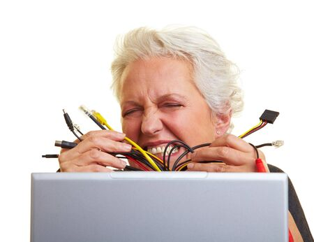 Senior woman at her laptop with many cables photo