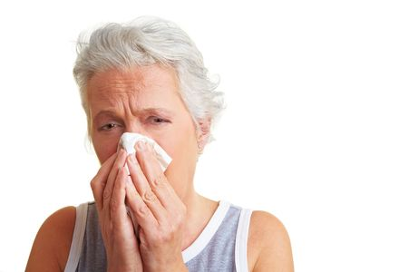 obscured: Senior woman blowing her nose with an handkerchief