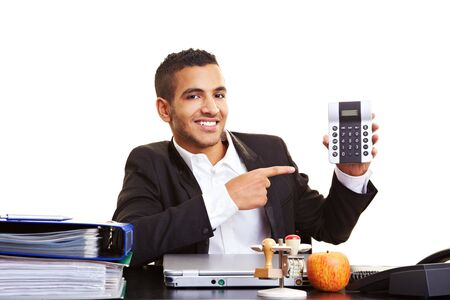 Young manager at his desk showing a calculator photo