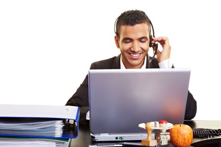 Young manager using a laptop with a headset photo