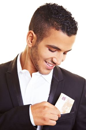 decadence: Young man putting banknotes in his jacket pocket Stock Photo