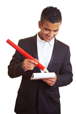 proportions of man: Young businessman holding an oversized red pencil