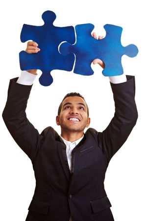 Happy businessman holding two blue jigsaw pieces photo