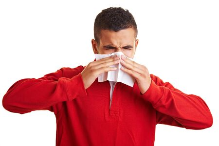 Young man sneezing in a paper handkerchief Stock Photo - 6408917