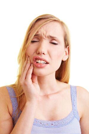 pangs: Giovane donna bionda con mal di denti tenendo la sua guancia