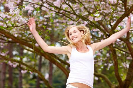 landschaft: Young woman under a blooming cherry tree Stock Photo