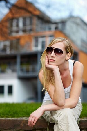 Young woman with sunglasses waiting in front of a house photo