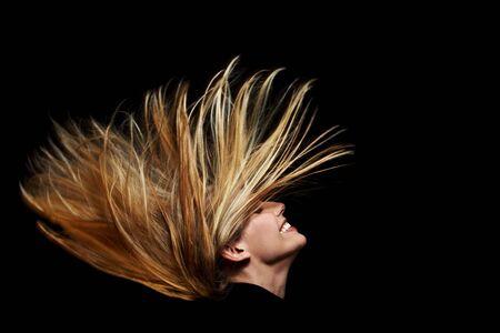 wild hair: Giovane donna bionda con agitando capelli nel buio
