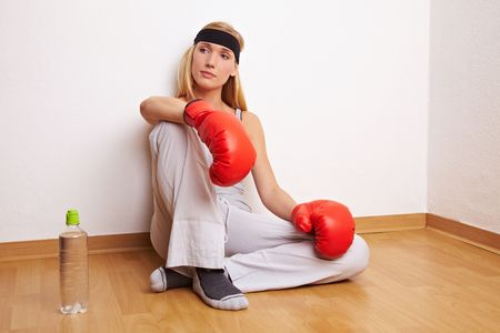 Young female boxer sitting on the floor photo