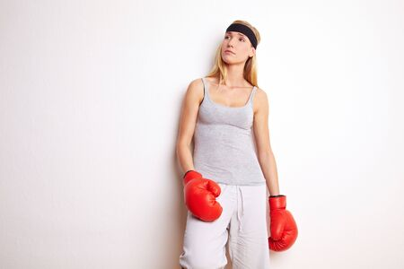 Young female boxer leaning on a white wall photo