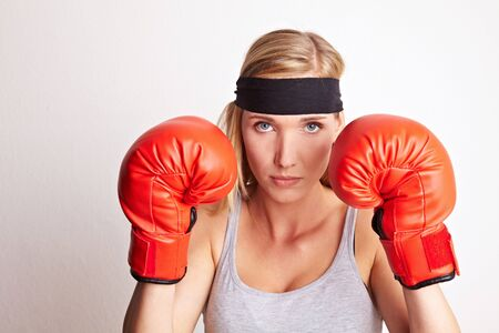 Young female boxer with red boxing gloves and headband Stock Photo - 6850248