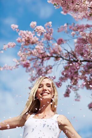 location shot: Young woman throwing pink cherry blossoms in the air Stock Photo