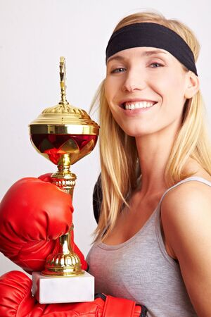 Young female boxer with red boxing gloves holding a trophy photo