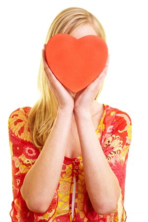 young woman holding a red heart in front of her face photo
