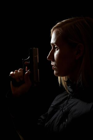Young female shooter holding a pistol at night photo
